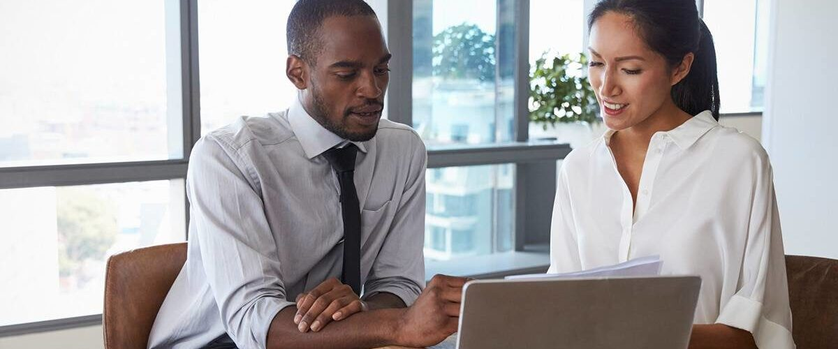 Image of businessman and businesswoman working in office and reviewing benefits of outsourcing payroll