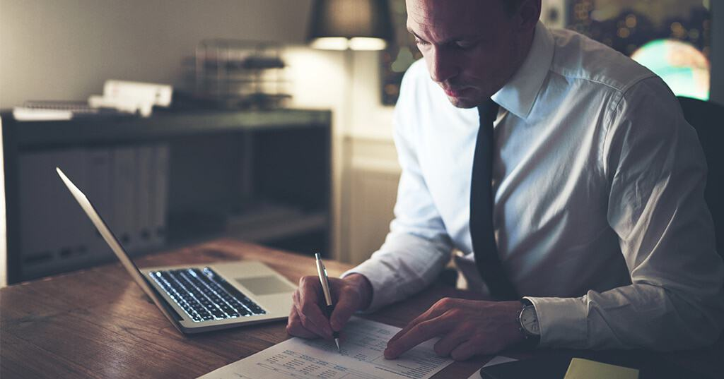 Image of accountant carefully reviewing document with new income tax withholding tables for 2018