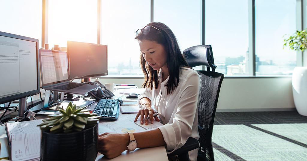Image of business woman reviewing charts and reports in office