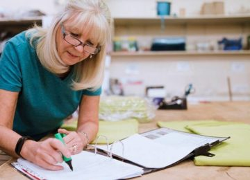 Image of older woman in home workshop reviewing her charitable contribution deductions