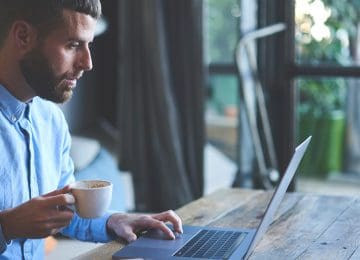 Image of man drinking coffee and using laptop to read about individual tax reform changes