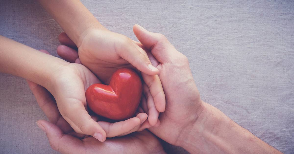 Image of two hands holding a red heart to represent charitable giving