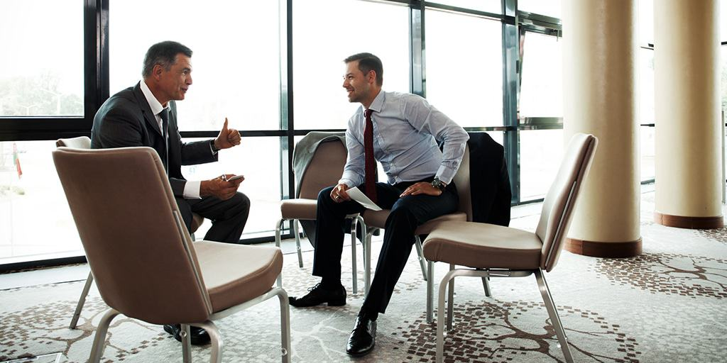 Image of two men in conference room discussing tax saving and how to apply deductions, exclusions, and credits