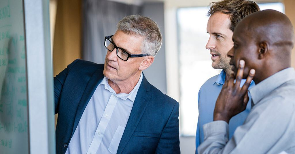 Image of three business men looking at whiteboard as one man outlines benefits of structuring business as a corporation