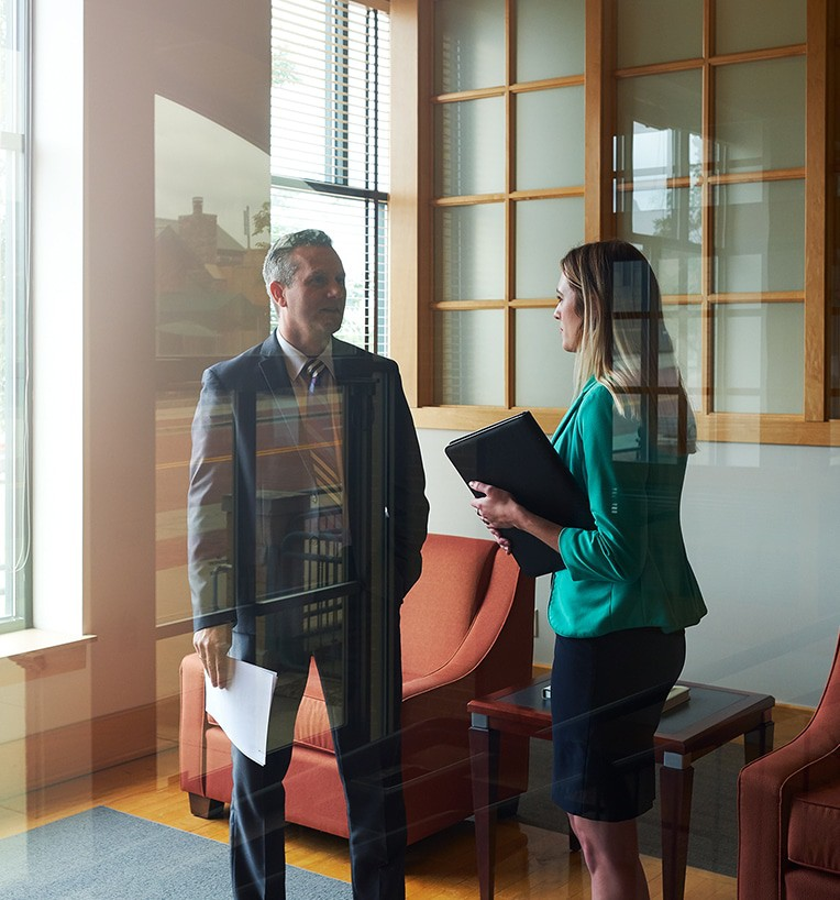 Two Beene Garter employees standing and talking in office lobby