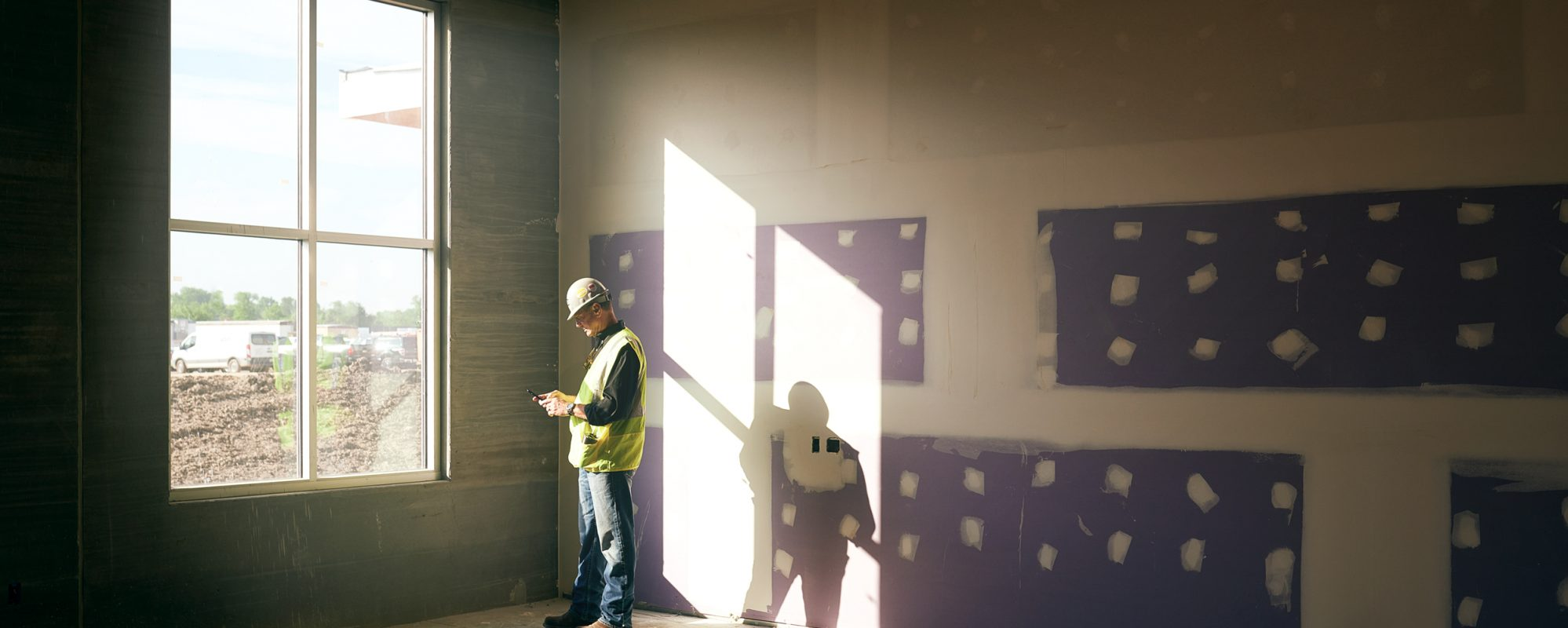 Image of construction worker checking phone at construction site