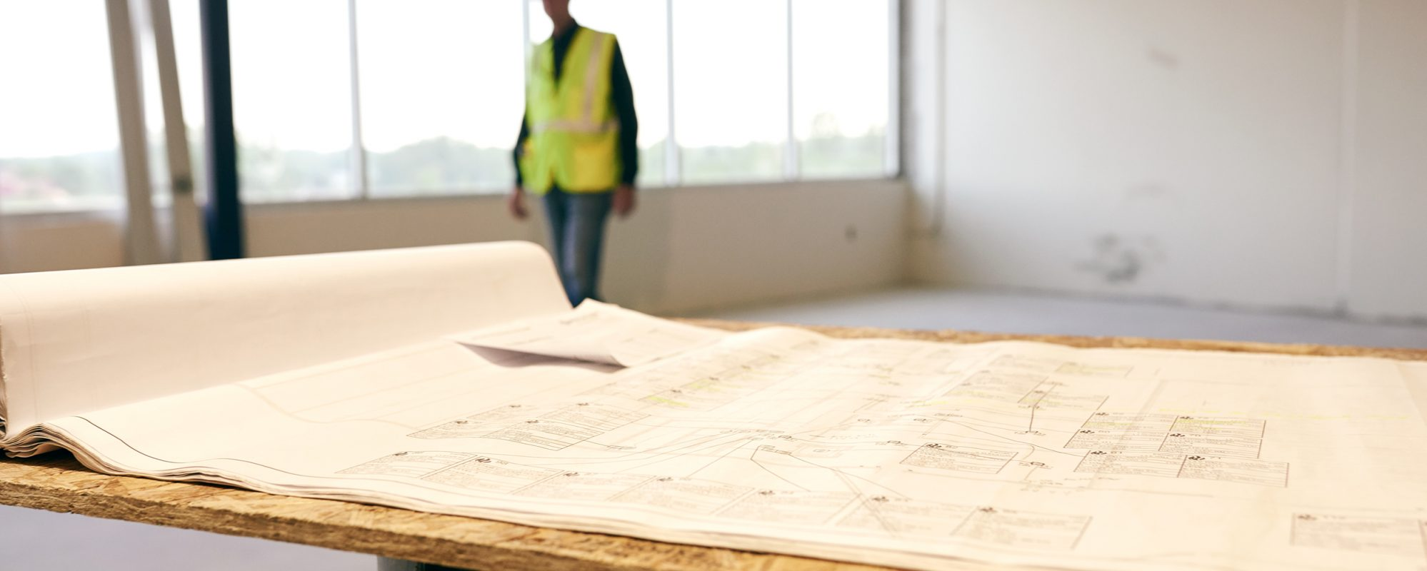 Image of construction plans and construction worker in background on Beene Garter's state and local tax page