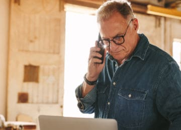 Senior male carpenter standing in workshop is targeted in social security number phone scam