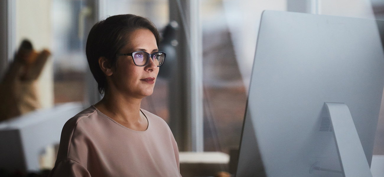 mature woman sits at computer and reads the new net operating loss rules under the cares act