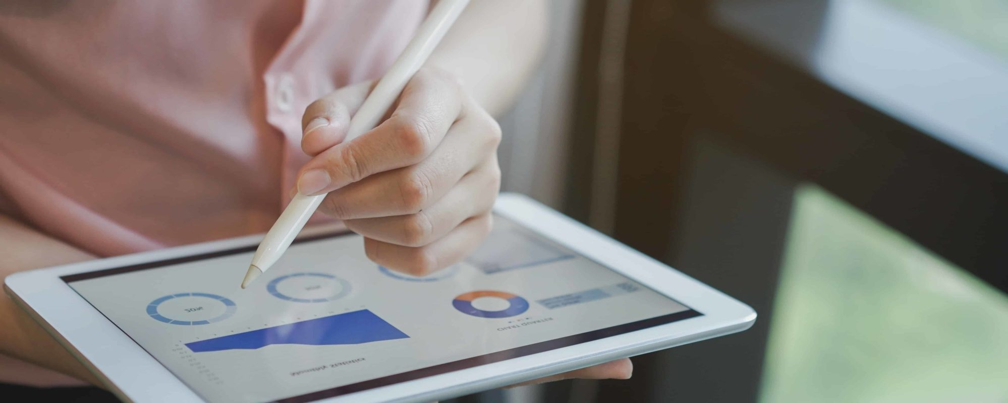 Close up on tablet's screen of accounting outsourcing software with financial reports and graphs