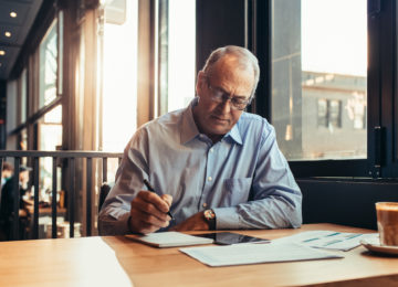 Mature man reviews important retirement planning ages in a cafe