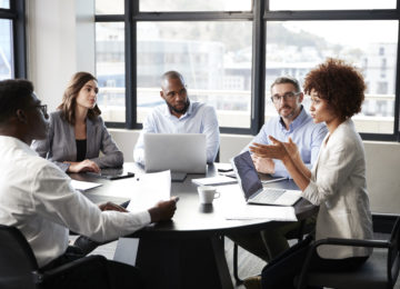 A group of employees discuss the different types of audits that best fit their business needs