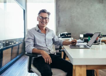 Mature businessman who qualifies for white-collar exemption sitting in office