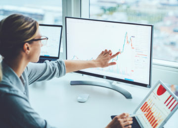 A woman reviewing real-time, financial and operational reports after struggling with QuickBooks' limitations