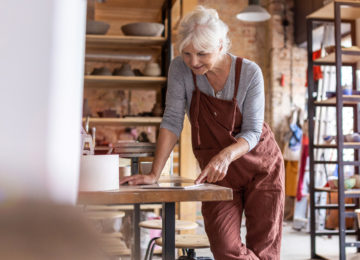 mature woman reviews retirement plan provisions in the cares act in her pottery studio