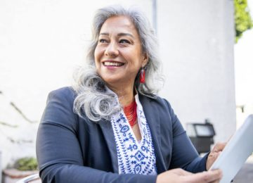 A businesswoman using a tablet to attend Data-Driven Nonprofit Finance Leader webinar