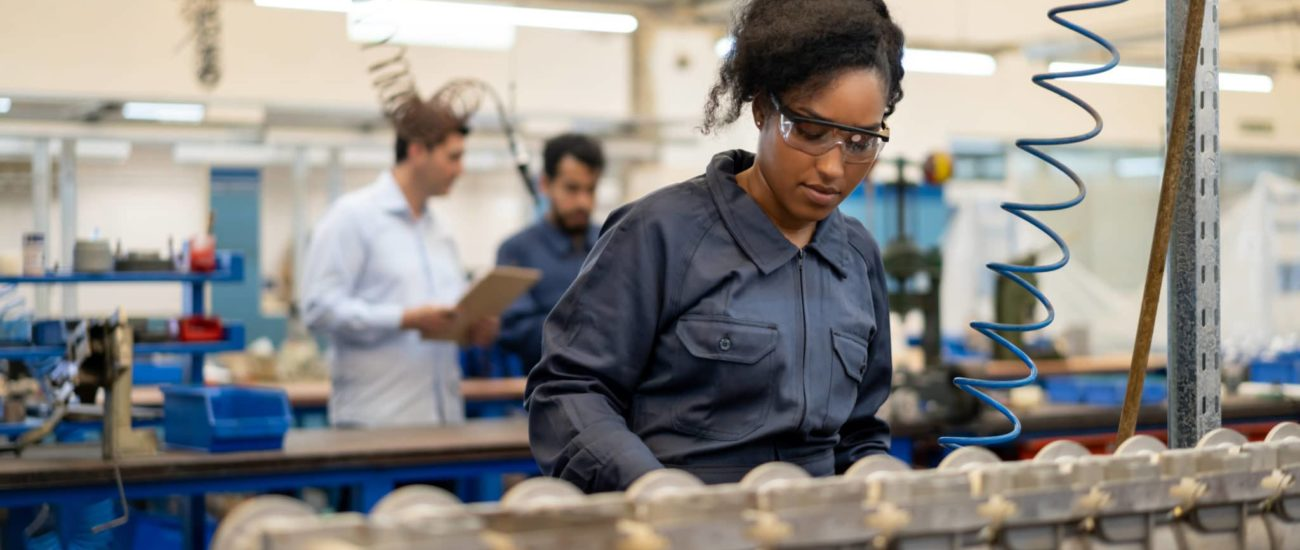 A young woman working at a factory that is considering switching payroll companies