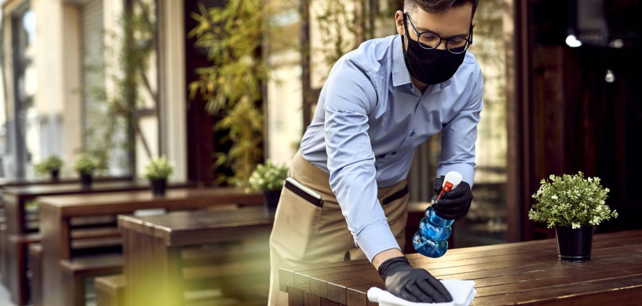 Young waiter cleaning tables after passing of American Rescue Plan Act of 2021