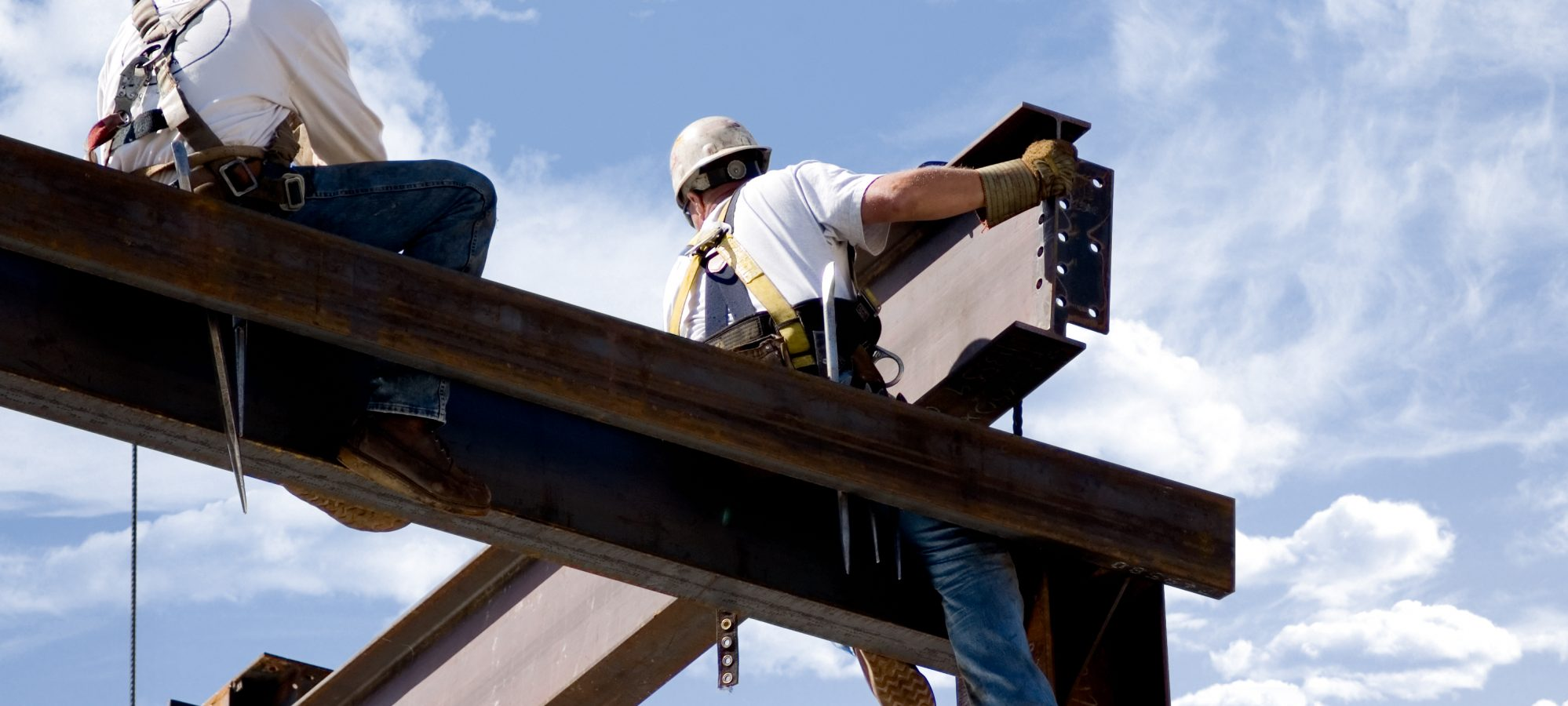 Image of two ironworkers putting up the skeleton of a building - contractors in Michigan