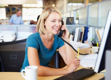 Image of woman talking on phone in office and paying state and local tax