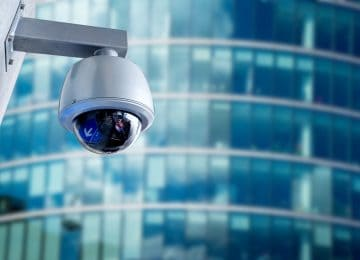 Image of security camera mounted on office building to detect fraud
