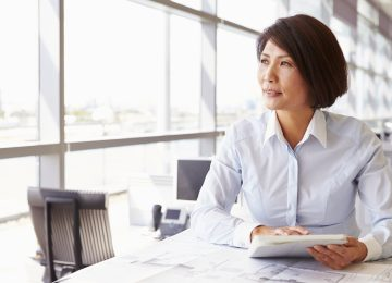 Image of business woman sitting in office and thinking about finding buyer for her business