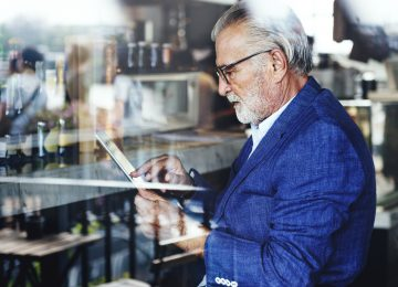 Image of older gentleman looking at tablet in bar and thinking about his succession plan