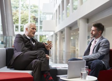 Image of two businessmen meeting in lobby area of office discussing business valuation