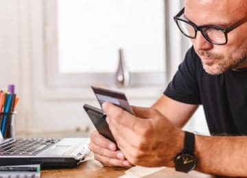 Image of man paying for online purchase with credit card on smart phone