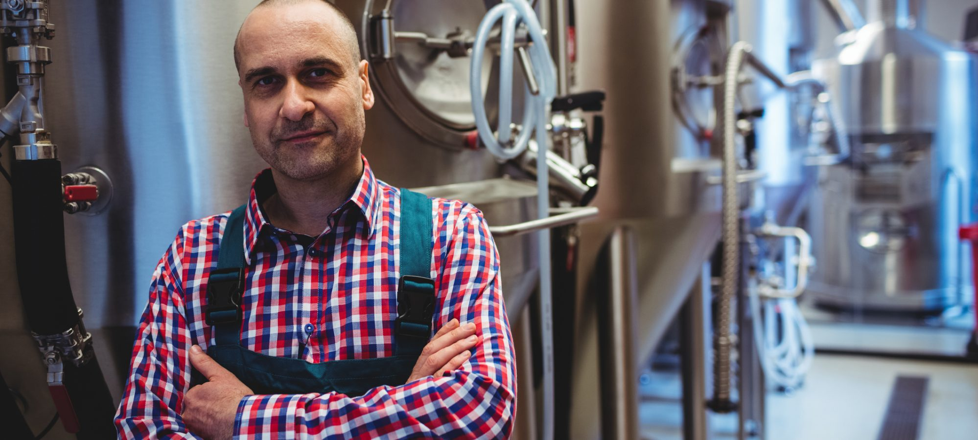 Image of man with arms crossed standing by storage tanks at brewery - retained earnings