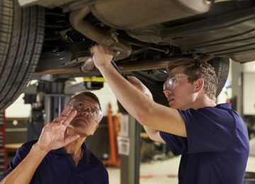 Image of mechanic and son working underneath car together - hiring your child in your business