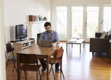 Image of man at home using laptop to access SafeSend Returns on dining table