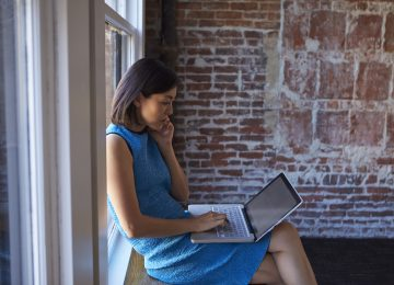 Business woman on laptop reviewing her nonprofit financial problems