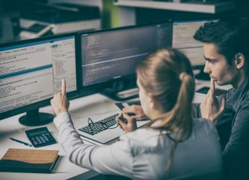 Image of IT developers working on coding and security technologies in office to prevent payroll fraud