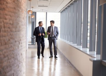 Image of two businessmen having informal meeting about qualified business income deduction in office corridor