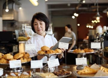 Image of business owner working in bakery shop, consider selling your business
