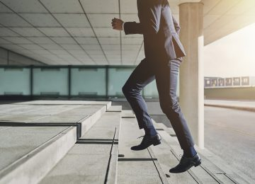 Image of businessman running up stairs in suit