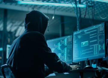 Image of hooded hacker breaking into data servers to enact a tax scam
