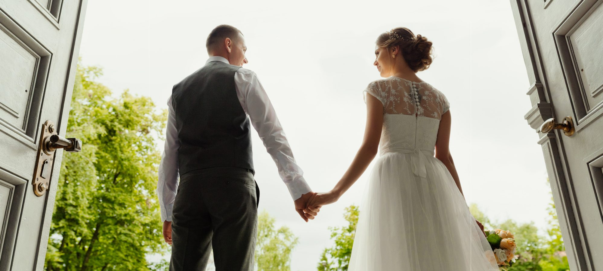Image of bride and groom - newlyweds - standing against the background of cathedral exit and holding hands