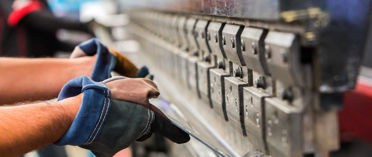 Image of man bending sheet metal in factory - tangible personal property or real property