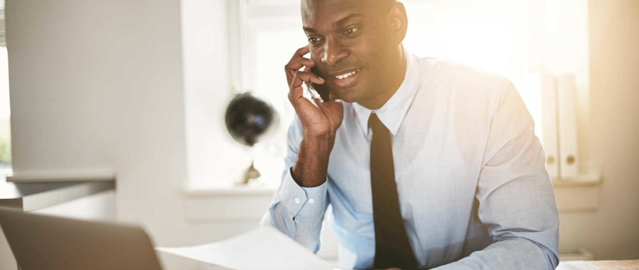 Image of young business professional talking on phone with accountant and discussing his SUW account