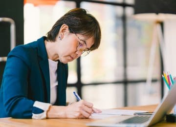 Image of middle age woman sitting at desk in office and calculating her 2018 QBI deduction