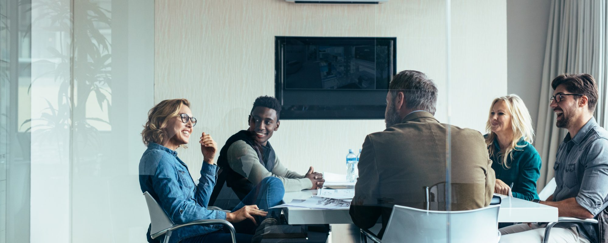 Image of business shareholders meeting in conference room and discussing the new partnership audit rules