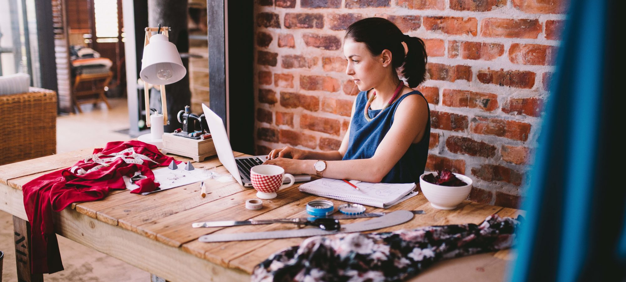 Image of young businesswoman working on laptop and documenting the fair market value of items