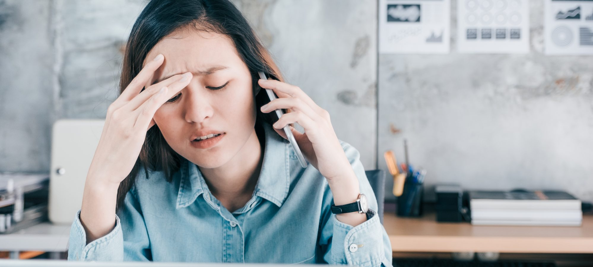 Image of young business woman who's on phone with current payroll provider and stressed