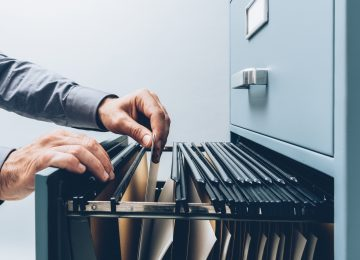 Image of person filing documents in filing cabinet - record retention