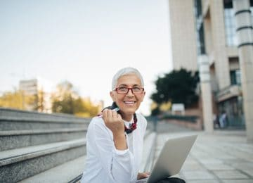 Image of older business woman sitting outside and planning for future