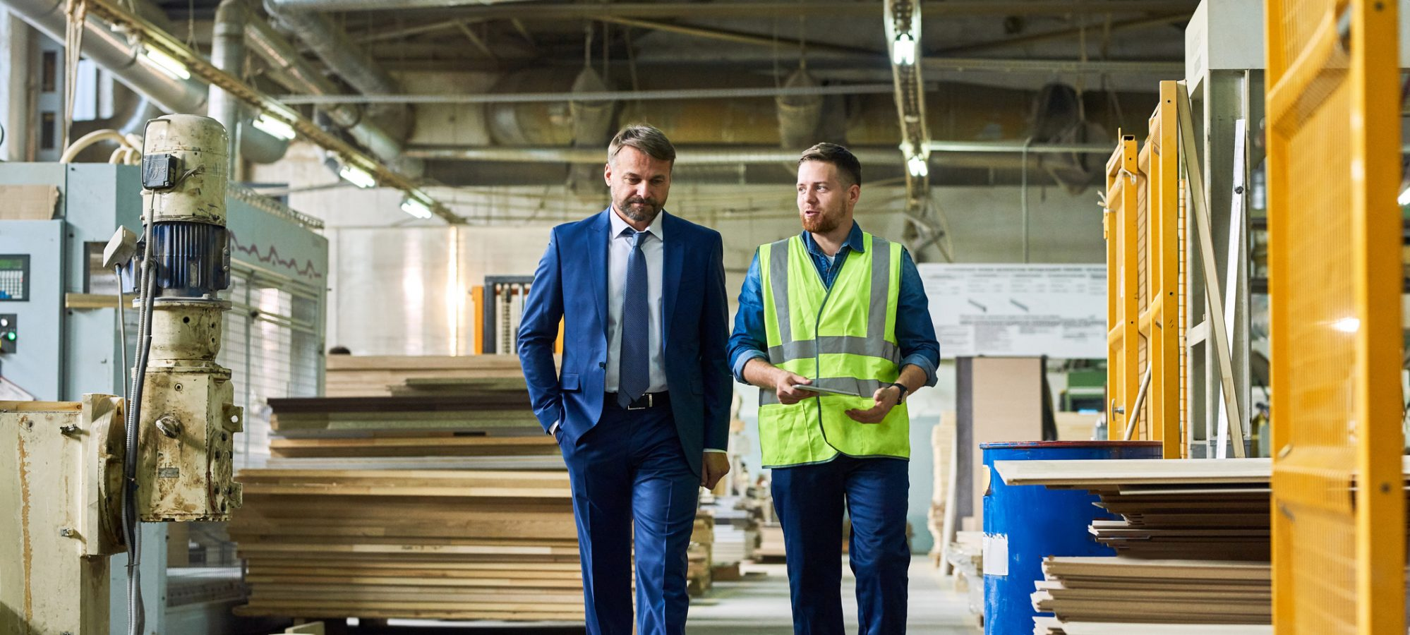 Image of young business owner giving tour of factory to ESOP valuation expert