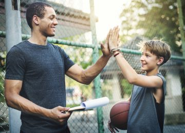 Image of young boy and volunteer coach high fiving after basketball practice