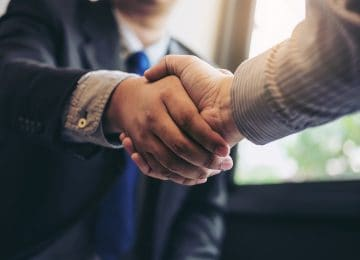 Image of two business men shaking hands during meeting - Sage Group and Intacct Corporation combine